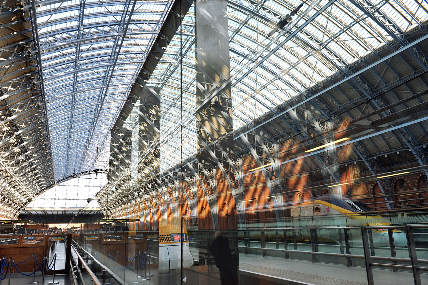 A view of the Champagne Bar and reflections of the girders and roof of the Barlow Shed, part of St Pancras International Station. Through the glass Eurostar trains can be seen on the tracks.